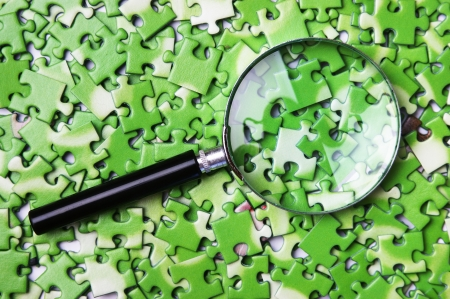 ecomomical: magnifying glass on pile of green puzzle