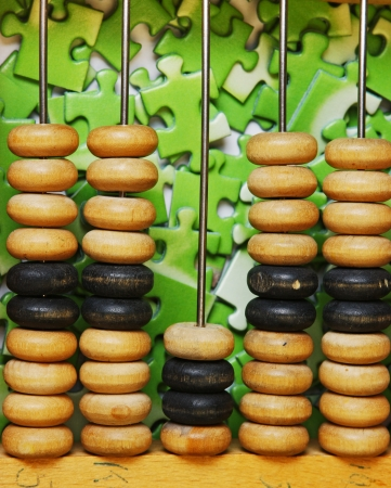 wooden abacus on pile of green puzzle Stock Photo - 15384595