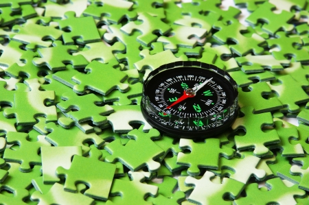 compass on pile of green puzzle photo