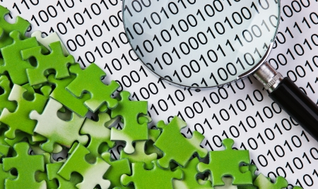 puzzles and magnifying glass on a binary code photo