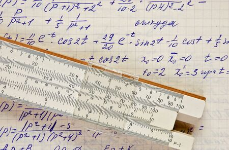 Page of old vintage paper with the calculation of the mathematics and slide rule photo
