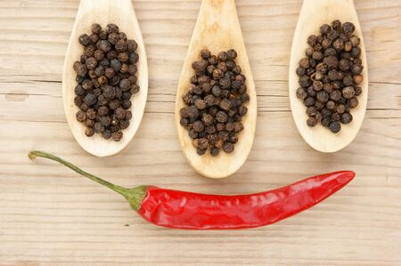 Black and red pepper in wooden spoon on the old board Stock Photo - 15572944