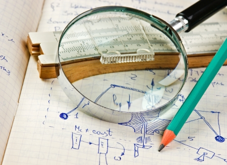 mathematical proof: magnifying glass and a slide rule on the old page with the calculations in mechanics