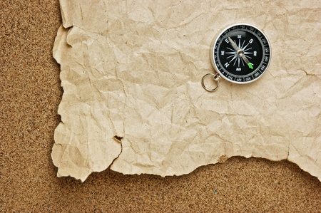 compass and old torn paper on a sandy beach photo