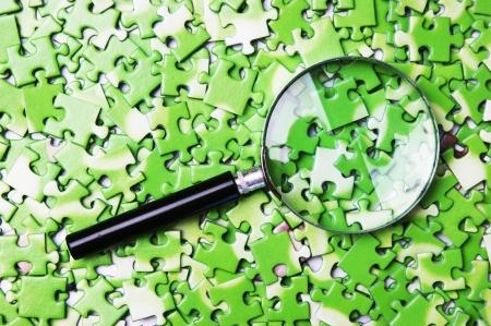 vergrootglas op stapel van groene puzzel Stockfoto