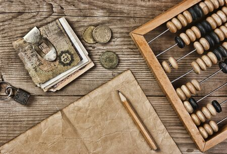 Old notes and coins and abacus on a wooden table Stock Photo - 15800157