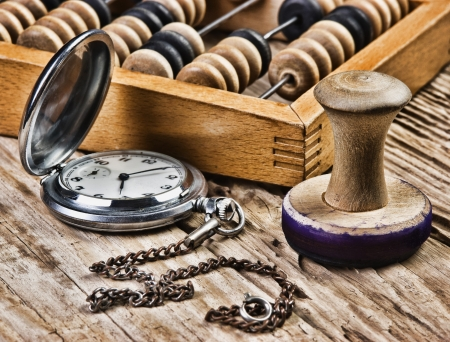 pocket watch, abacus and stamp on a wooden table Stock Photo - 15885225
