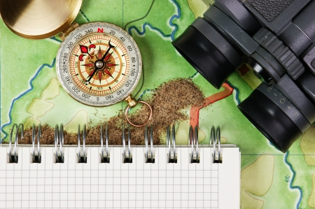 cartographer: binoculars and a compass on the map with sand Stock Photo