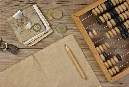 abaco: Billetes y monedas antiguos y ábaco sobre una mesa de madera Foto de archivo