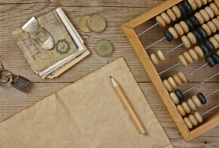 an abacus: Old notes and coins and abacus on a wooden table