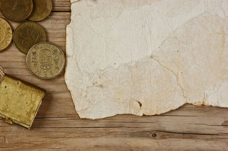 Old paper and coins on a wooden table photo