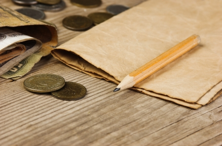 Old notes and coins and pencil on a wooden table Stock Photo - 15886379