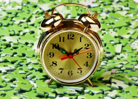 alarm clock on pile of green puzzle