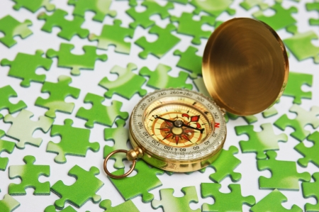 technology metaphor: compass on the green puzzle Stock Photo