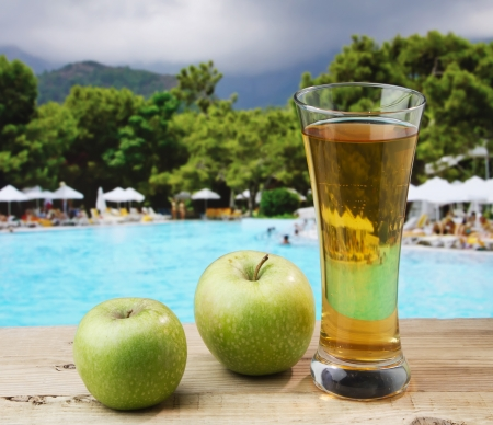 Glass of apple juice on a beach table  photo