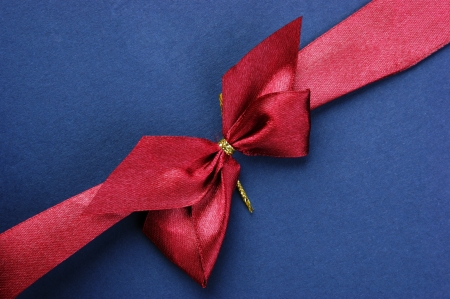 Blue Christmas gift box with red bow and ribbon photo