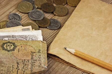 Old notes and coins and pencil on a wooden table Stock Photo - 16283290
