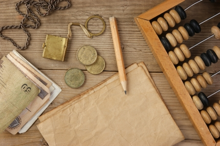 Old notes and coins and abacus on a wooden table photo