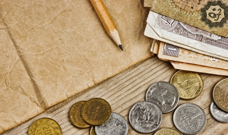Old notes and coins and pencil on a wooden table Stock Photo - 16646694