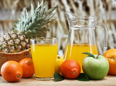 variety of fruit and juice on a wooden table in the garden photo