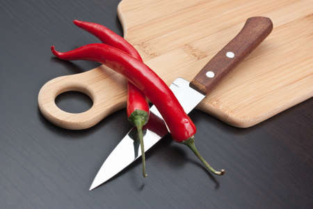 Two red cayenne and knife on the kitchen table photo