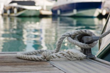afmeren touw met een geknoopte uiteinde gebonden rond een kikker op een houten pier Stockfoto