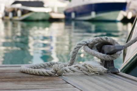mooring rope with a knotted end tied around a cleat on a wooden pier Stock Photo