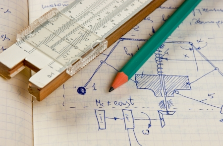 pencil and a slide rule on the old page with the calculations in mechanics photo