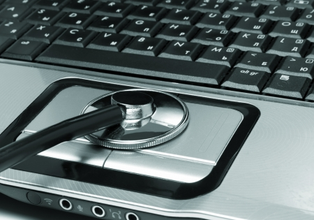 Medical stethoscope and open laptop photo