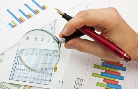 financial figure: magnifying glass in hand and working paper chart