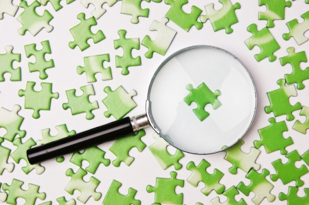ecomomical: magnifying glass on the green puzzle Stock Photo