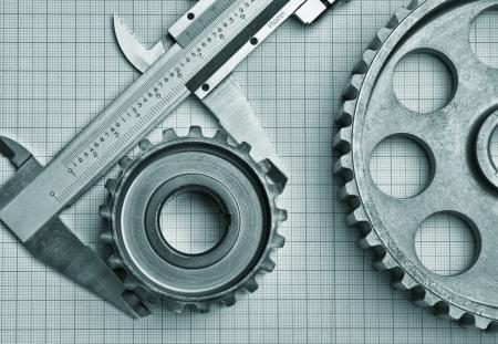 herramientas de mec�nica: engranajes y la pinza en un papel cuadriculado