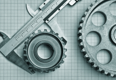 mechanical engineering: gears and caliper on graph paper Stock Photo