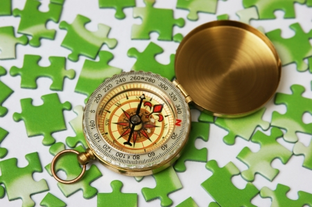 compass on the green puzzle Stock Photo - 17625413