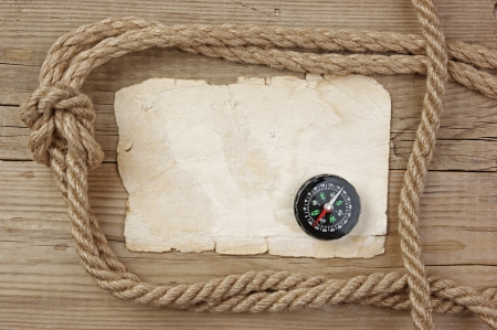 Vintage paper with compass and rope on old wooden boards photo