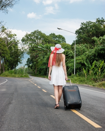young girl walking down the road with a suitcase photo