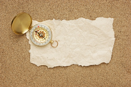 compass and old torn paper on a sandy beach Stock Photo - 18214638