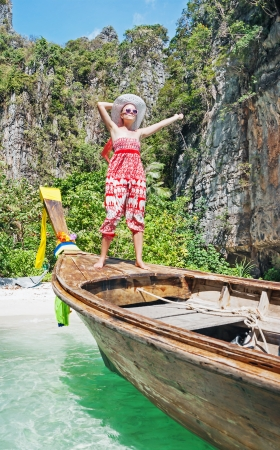 A young girl stands on Thai Longtail boat on the beach Maya Bay Phi Phi, Thailand photo