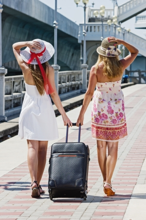 Two young girls walk along the road with a suitcase