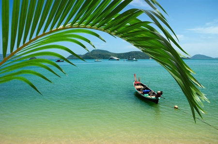 lonely boat on the beach of tropical island photo
