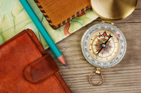 compass wallet and passport on a wooden table photo