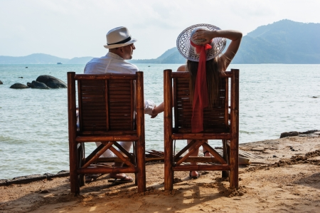 young man and woman sitting on the beach and holding hands photo
