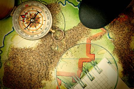 compass and  notebook on the map with sand photo