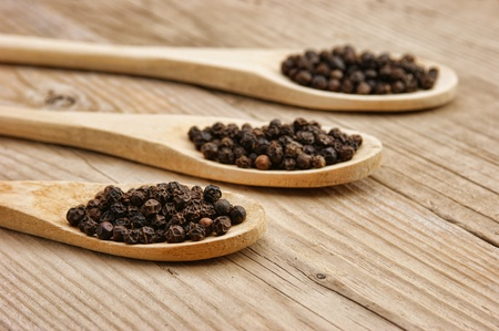 Black pepper in wooden spoon on the old board Stock Photo - 18726649