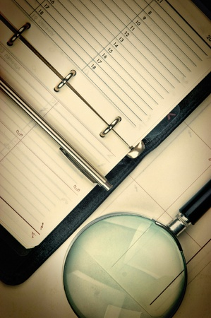 pen, magnifying glass and the diary  photo
