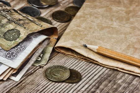 Old notes and coins and pencil on a wooden table photo
