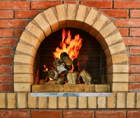 stone fireplace: Russian interior kitchen with an oven and a burning fire Stock Photo