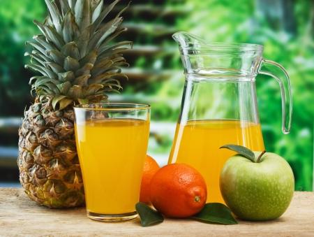 verscheidenheid van fruit en sap op een houten tafel in de tuin