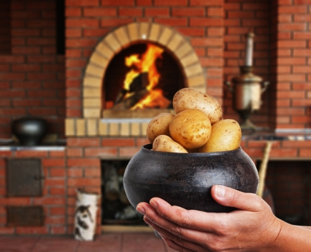 cast iron pot with a potato in the hands in Russian cuisine  with an oven and a burning fire photo