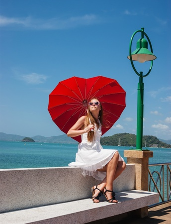 young girl with a red umbrella sits on the waterfront and looks at the sea photo